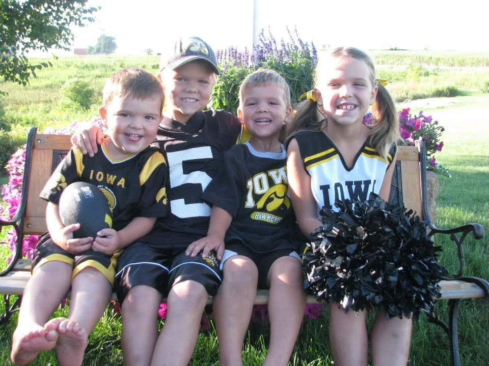 My small children sitting on a bench outside dressed in their Iowa Hawkeyes outfits