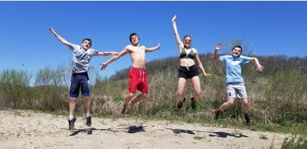 My four kids jumping in the air on a river bank on a beautiful summer day