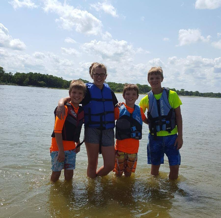 Kids standing together in the river wearing life jackets