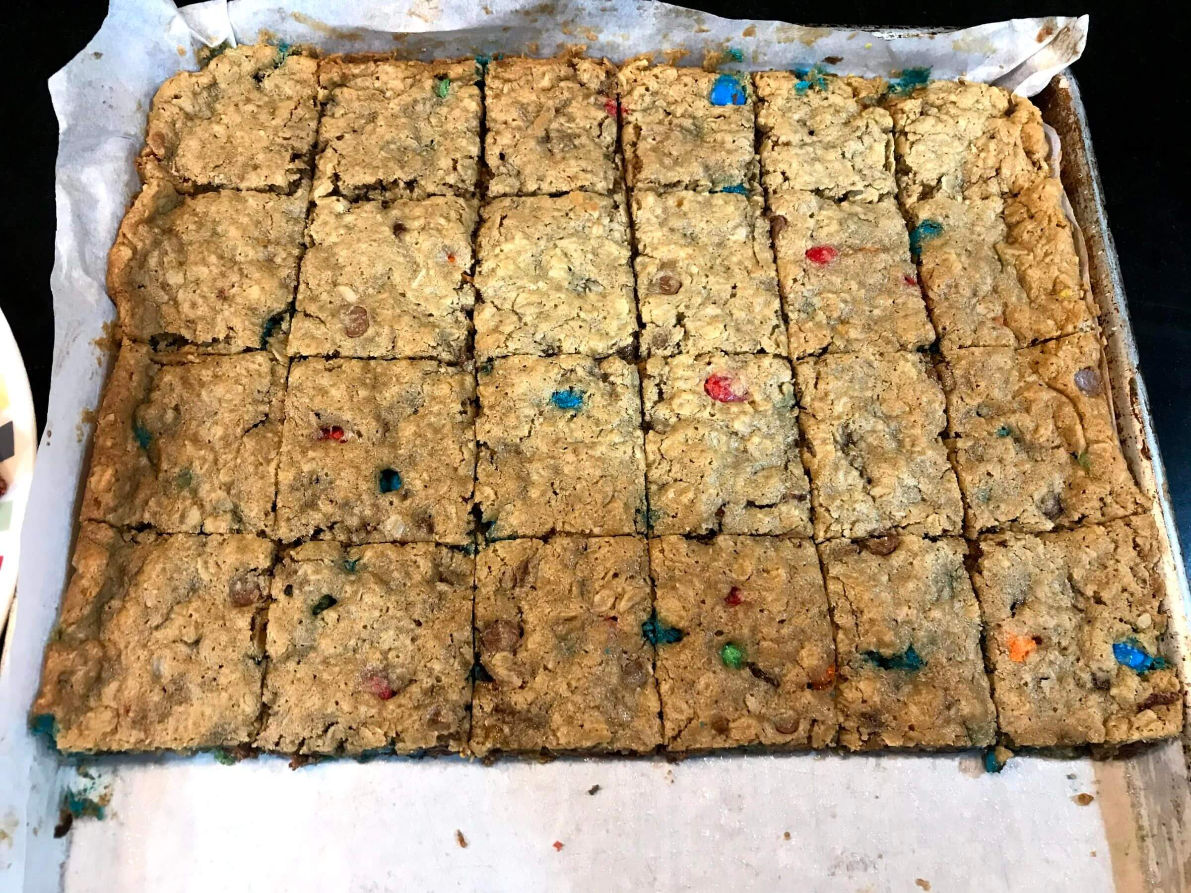 Gluten free monster cookie bars on parchment paper