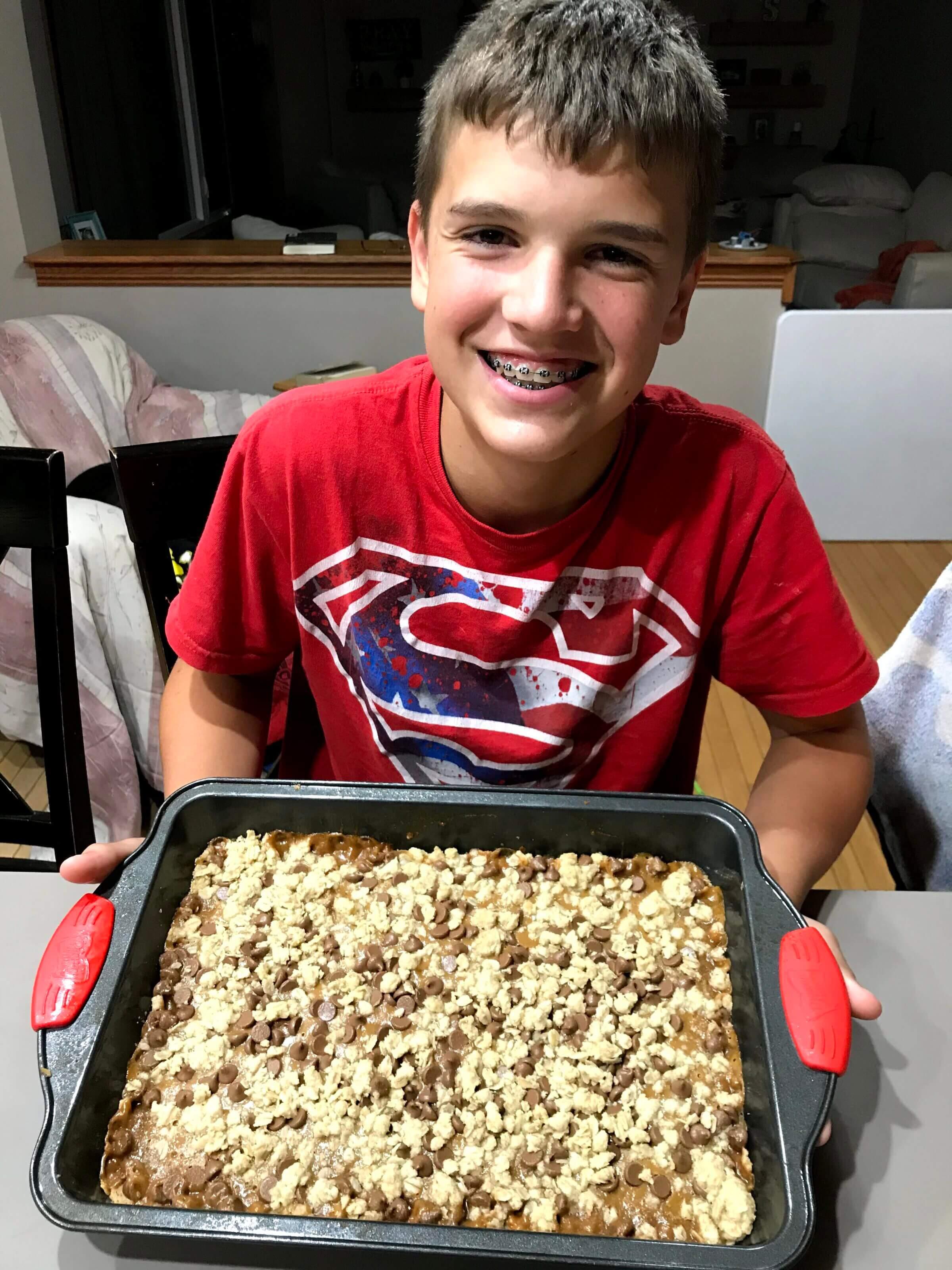 Boy with pan of chocolate caramel oatmeal chews