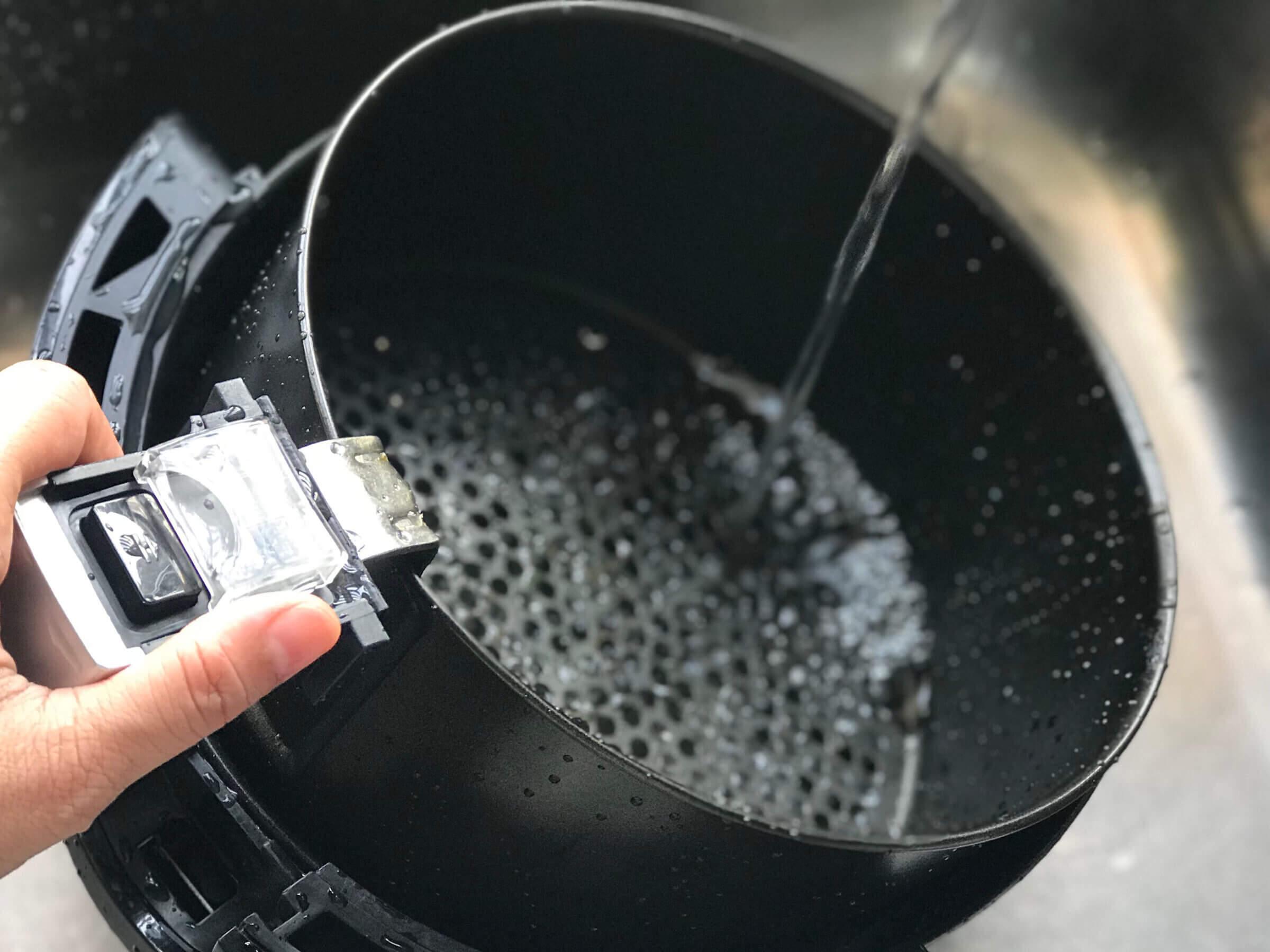 Air fryer basket being washed under running water