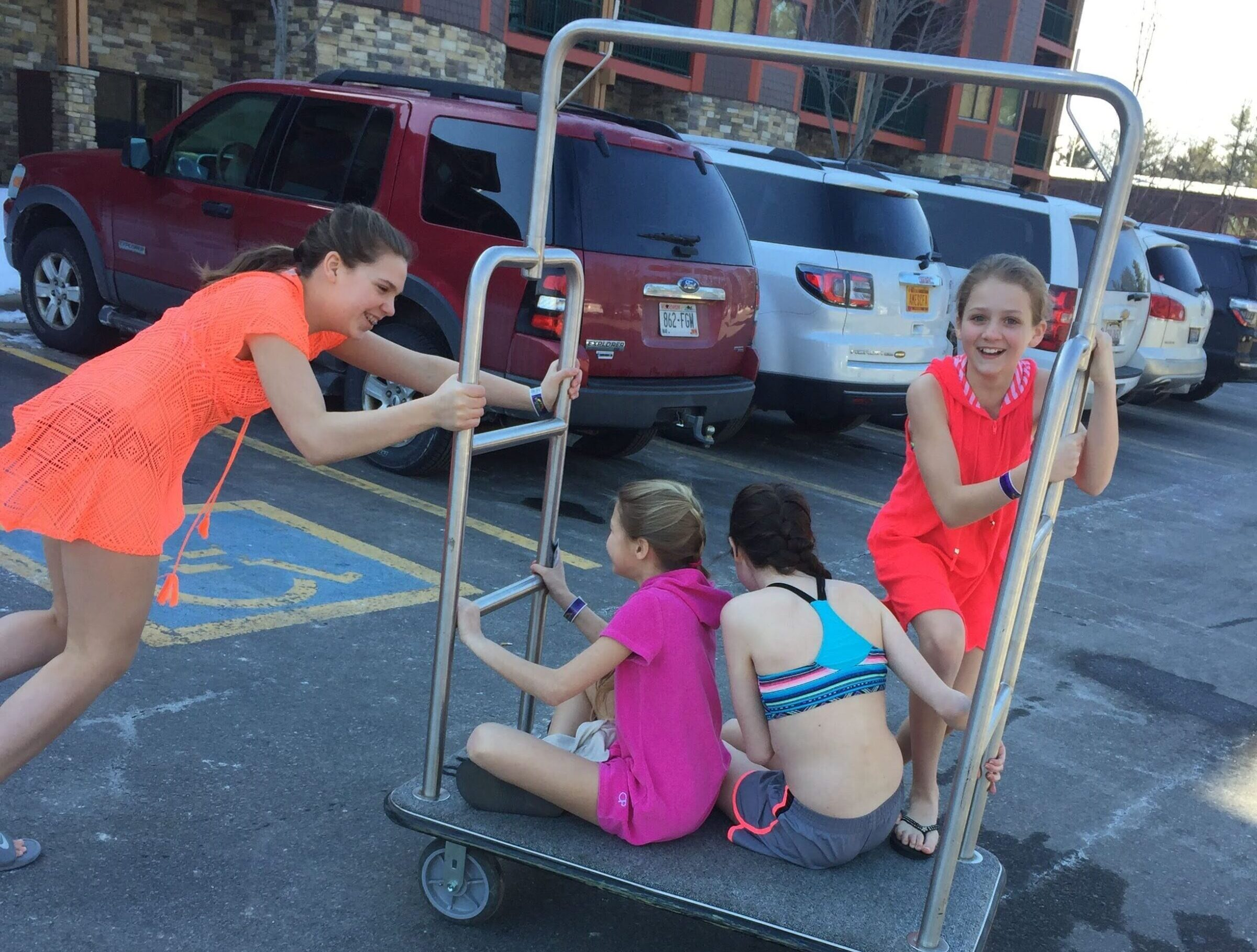 Girls taking a ride on luggage cart in hotel parking lot
