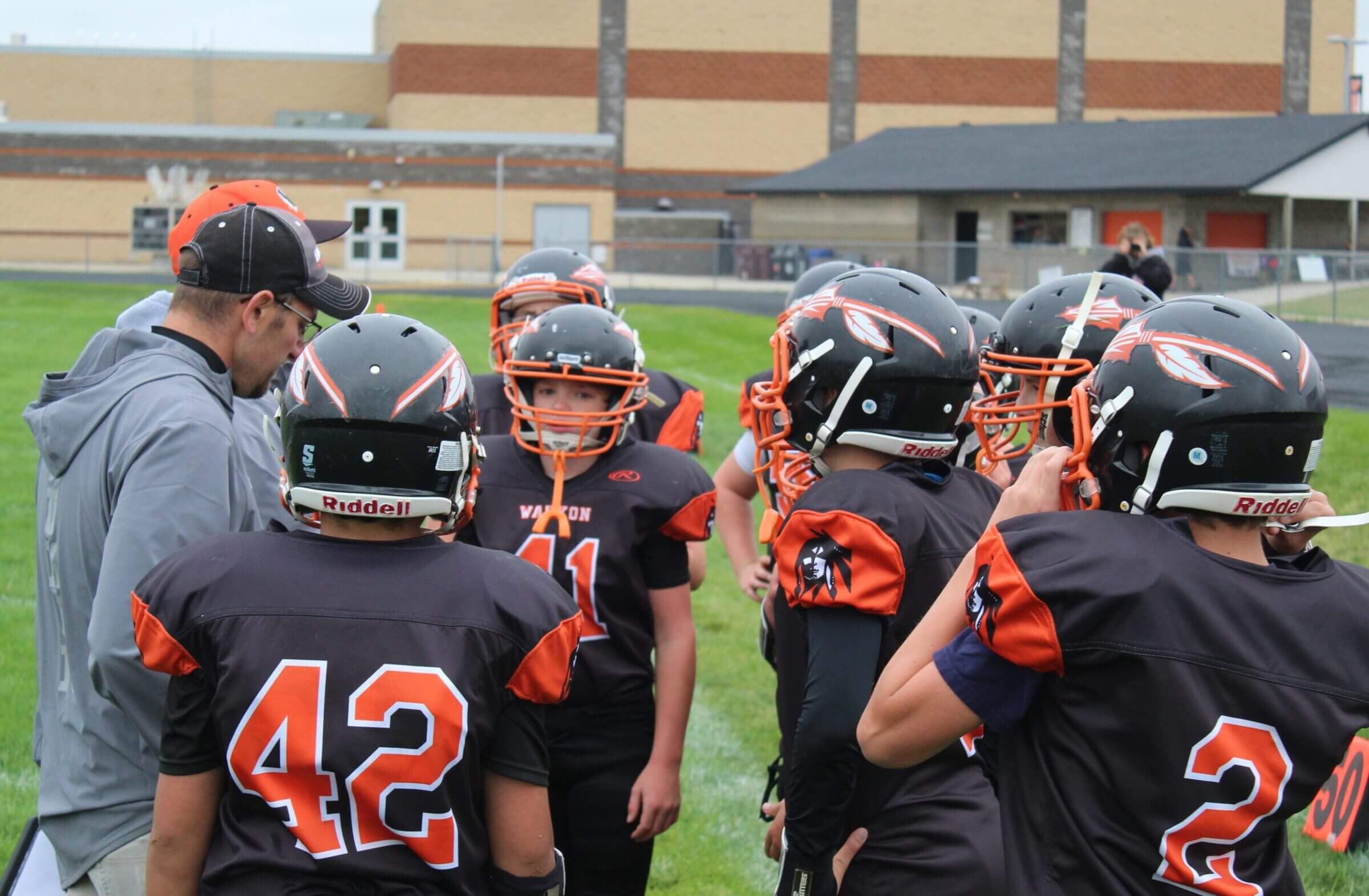 Football team in the huddle at practice