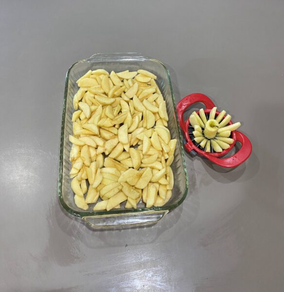 Sliced apples in pan with thin apples slicer shown slicing apples